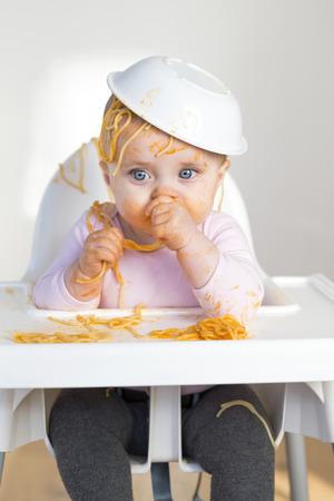 어린 소녀 그녀의 저녁 식사를 먹고 엉망으로 만드는.