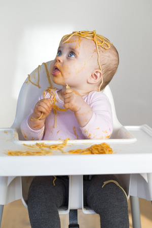mess: Little Girl Eating her dinner and making a mess.