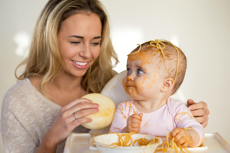 Mother laughing as she tries to clean up her messy baby  who is eating spaghetti in a high chair.