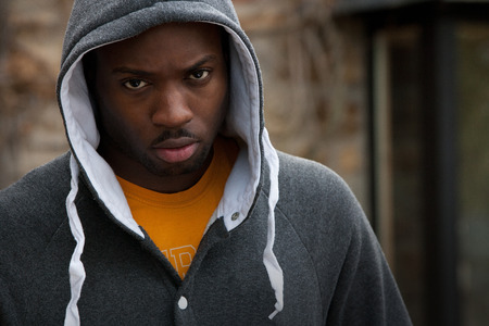 Young man with his hood up looking angrily at the camera