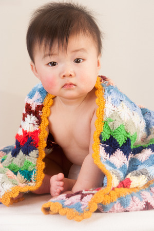 hair wrapped up: Cute Asian baby sitting with a colourful, knitted blanket round him.