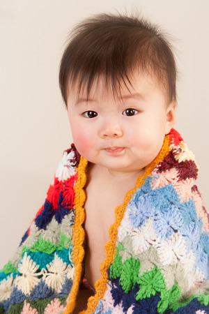 hair wrapped up: Cute Asian baby sitting with a colourful, knitted blanket round him Stock Photo