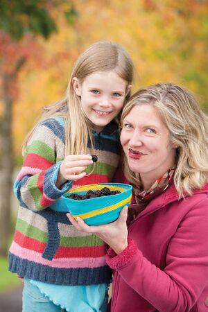 messily: Mother and daughter messily sharing blackberries Stock Photo