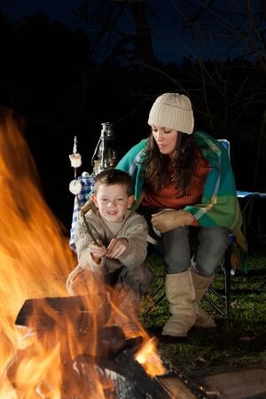 whilst: Little boy is sitting with his mother at a bonfire whilst roasting marshmallows. Stock Photo