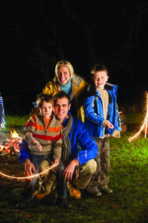bonfire night: Brothers posing with sparklers on bonfire night with their parents Stock Photo