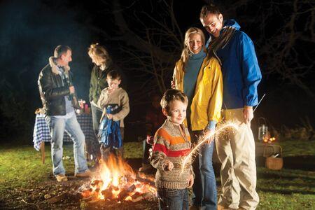 庭の焚き火を楽しみ、花火で遊んで家族 写真素材