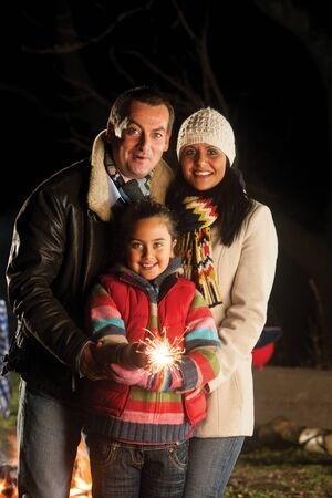 bonfire night: Young girl posing with a sparkler on bonfire night, with her parents