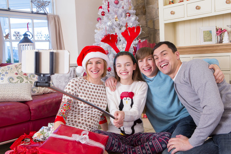 christmas decorations: Two Generation Family taking a Selfie at Christmas. They are wearing novelty items and Smiling at the Camera.