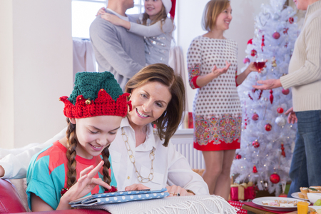 granny and grandad: Three Generation Family at Christmas Time. A young girl and her grandma focus on the tablet while the rest of the family socialises in the background. Stock Photo