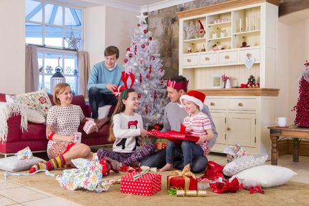 two generation family: Two Generation Family opening presents at christmas time. They are looking at each other and wearing christmas clothing. Stock Photo