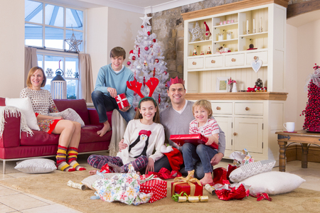 two generation family: Two generation family in front of a christmas tree opening presents. They are all dressed for christmas and smiling at the camera.