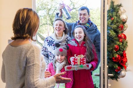 Familie leveren Presents in de kersttijd. Ze zien er allemaal blij en klaar om te vieren. Stockfoto