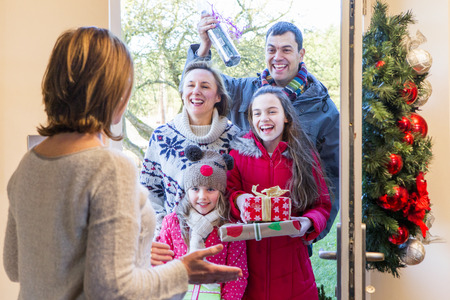 Family delivering Presents at Christmas time. They all look happy and ready to celebrate.
