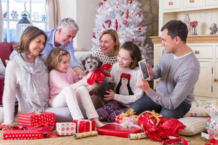 embrace family: Papá toma una foto de familia de tres generaciones en el tiempo de Navidad. Todos parecen entusiasmados con su nuevo cachorro. Foto de archivo