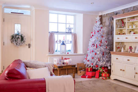 door man: A Horizontal Image of a Living Room dressed for Christmas. Colours mainly Red and White and spacious. No People. Stock Photo