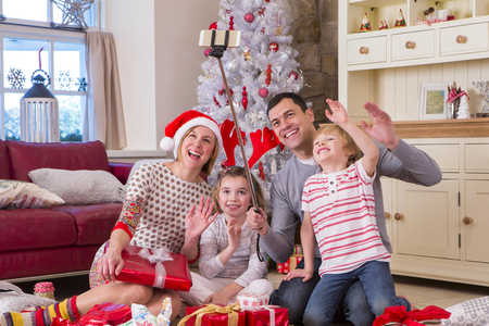 two generation family: Two Generation Family taking a Selfie at Christmas. They are using a Selfie Stick and waving at the Camera.