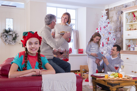 three generation: Three Generation Family at Christmas Time. Young Girl is looking at the Camera and Smiling while the family chat in the background. Stock Photo