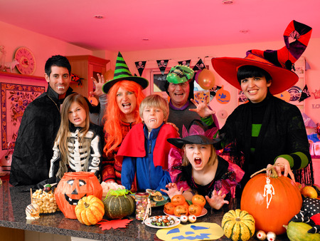famiglia: Familyfriends posa per la macchina fotografica nei loro costumi halloween. Essi sono in piedi in cucina con cibo partito e dolcetti di cui di fronte a loro. Archivio Fotografico