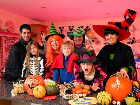 famille: Familyfriends posant pour la caméra dans leurs costumes d'Halloween. Ils sont debout dans la cuisine avec de la nourriture du parti et friandises énoncées en face d'eux.