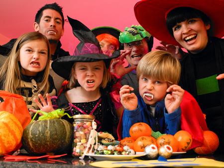 Familyfriends posa per la macchina fotografica nei loro costumi halloween. Essi sono in piedi in cucina con cibo partito e dolcetti di cui di fronte a loro. Archivio Fotografico - 42278246