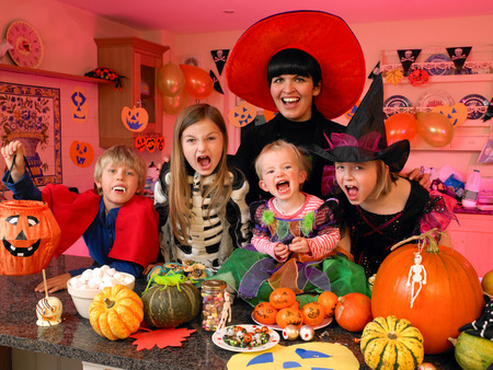 Familyfriends posing for the camera in their halloween costumes. They are standing in the kitchen with party food and treats set out in front of them.