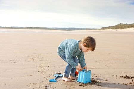 openness: Little boy digging on the beach with a bucket.