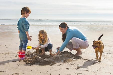 Moeder spelen op het strand met haar zoon en dochter, met hun hond hen vergezellen. Stockfoto
