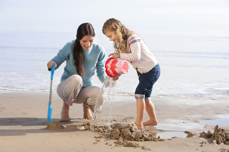 late summer: Mother digging in the sand on the beach with her daughter. Stock Photo