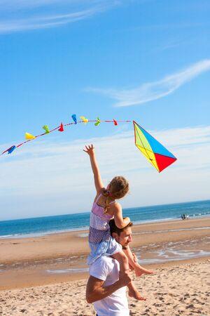 Padre llevar a su hija en sus hombros mientras ella vuela una cometa en la playa