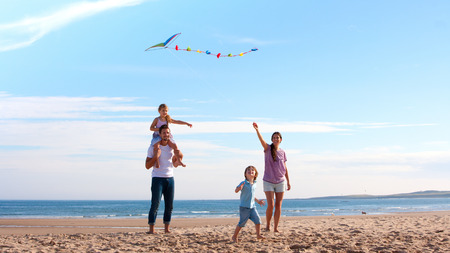 family bonding: Family of four flying a kite together on the beach