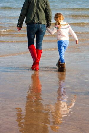 girls holding hands: Mother and daughter walking along the beach Stock Photo