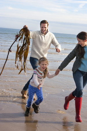 Father chasing his daughter and partner with seaweed on the beach