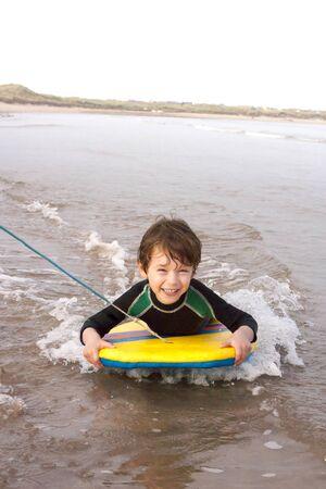 bodyboarding: Little boy being pulled along the coast on a body board