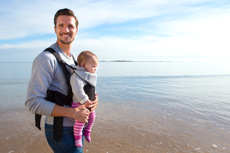 Father carrying his baby daughter along the beach Foto de archivo