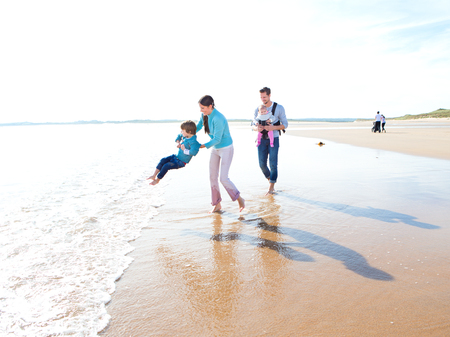 family playing: Family of four walking and playing on the beach Stock Photo