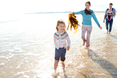 silliness: Mother chasing eldest daughter with seaweed on the beach with father and baby daughter behind them Stock Photo