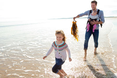 silliness: Father with baby chasing his eldest daughter with seaweed on the beach