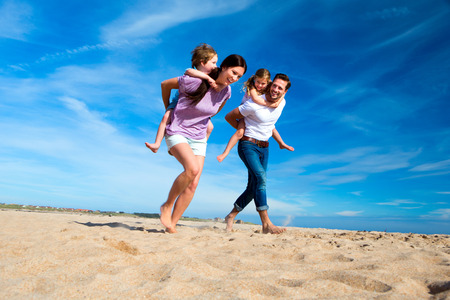 Mother and Father piggybacking their children on the beach Stockfoto