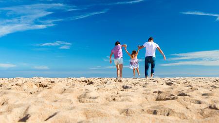 Rodiče kyvné jejich dceru na pláži Reklamní fotografie