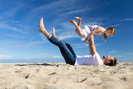 affectionate actions: Father lying on the beach holding his daughter in the air.