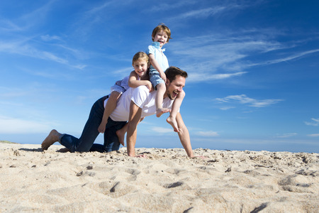 father's: Father on the beach with his son and daughter riding on his back