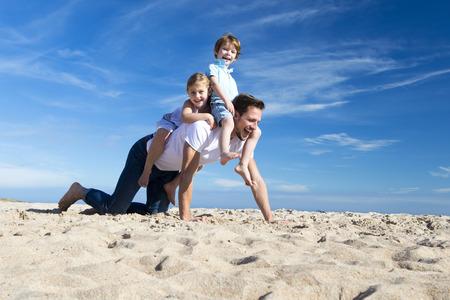 padres: Padre en la playa con su hijo e hija de montar en su espalda