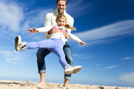 family with one child: Father swinging his daughter round on the beach