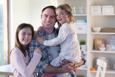family and home: Father smiling for the camera with his daughters at home