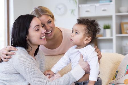 自分の赤ちゃんの息子と一緒に遊んで、自宅で座っている女性のカップル。