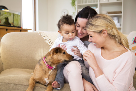 Same sex female couple sitting with their son and dog on the sofa in their home
