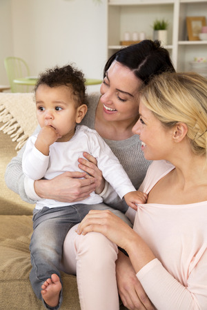 Same sex femal couple sitting with their son at home