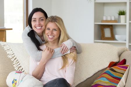 sex: jonge vrouw staat achter haar partner zitten op de bank met haar armen om haar heen. Ze zijn allebei lachend naar de camera