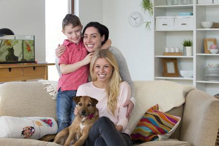 sexo: Pareja de mujeres con el hijo y perro posando para la cámara en su casa
