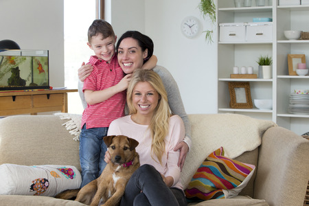 Female couple with son and pet dog posing for the camera in their home Stockfoto